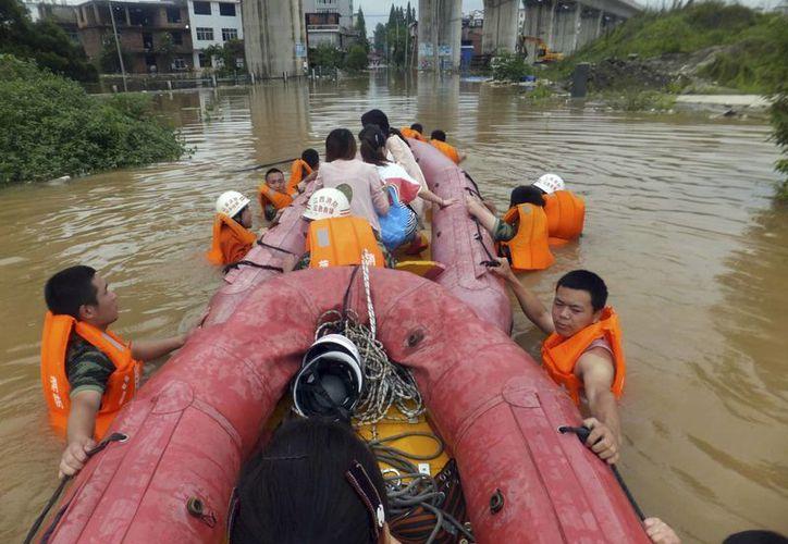 Cuadrillas de rescatistas evacuan a residentes en lanchas de goma en esta foto tomada ayer en las calles inundadas del condado Shangli de la provincia Jiangxi, en el área central de China. (Milenio Novedades)