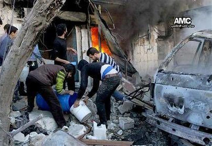 Civiles llenan cubos de agua para extinguir las llamas de un establecimientos que sufrió daños por el ataque aéreo del gobierno sirio. (Agencias)