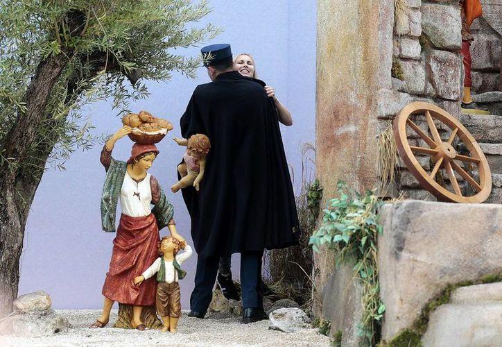 Un agente de la Gendarmería del Vaticano detiene a una supuesta activista de Femen, quien en la foto aún sostiene al niño Jesús que pretendía llevarse. (EFE)
