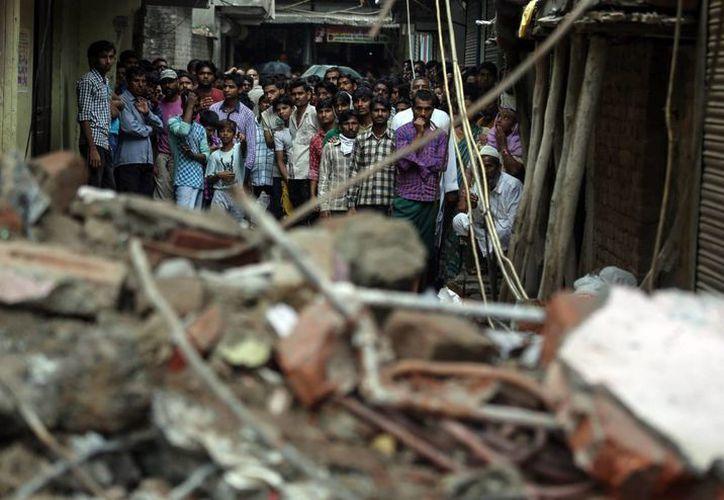 Vecinos y curiosos siguen de cerca las labores de rescate en el edifico derrumbado la mañana del domingo en Nueva Delhi, India. (EFE)