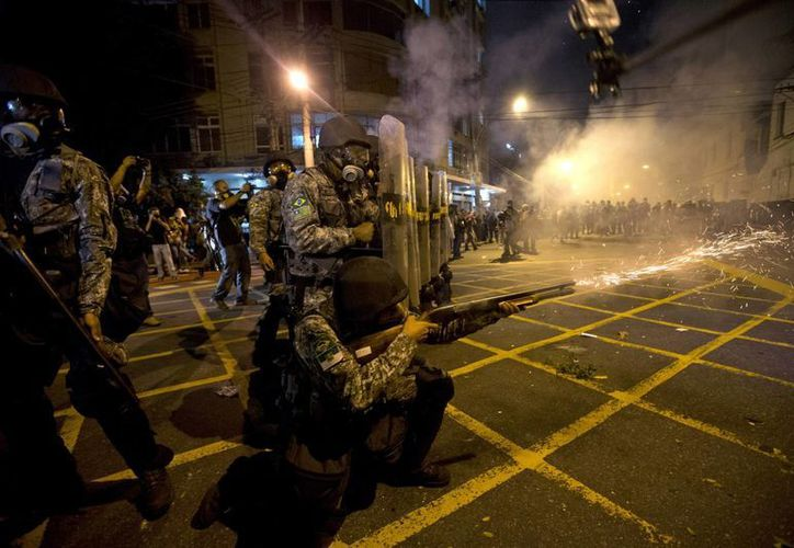 Esta fotografía del 30 de junio del 2013 muestra a la policía militar mientras dispara gases lacrimógenos cerca del estadio de Maracaná en el partido final entre España y Brasil durante la Copa Confederaciones en Río de Janeiro, Brasil. (Agencias)