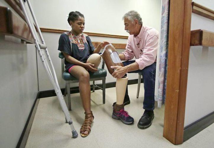 Paul Martino, presidente de United Prosthetics, habla con Mery Daniel, sobreviviente del ataque contra el Maratón de Boston. (Agencias)