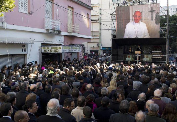 Los asistentes al acto en homenaje a las víctimas de un atentado antisemita en Argentina en 1994 observan un mensaje grabado enviado por el Papa Francisco, quien se unió a los familiares de las 85 víctimas en su reclamo de justicia en Buenos Aires. (Agencias)