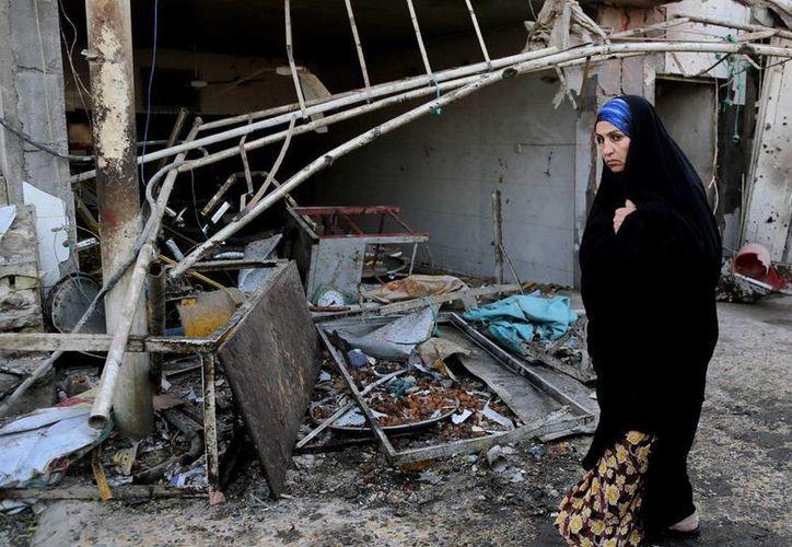 En las últimas horas, al menos 33 personas ha muertos en atentados en Irak. En la imagen, una mujer camina frente a uno de lo lugares en donde estalló un coche bomba, en Bagdad. (Agencias)