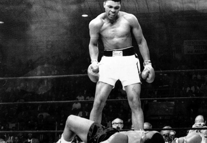En la imagen, Cassius Clay (de pie) vocifera tras derribar a su oponente, Sonny Liston, al minuto de iniciarse el combate para el título Mundial de los pesos pesados. (EFE)