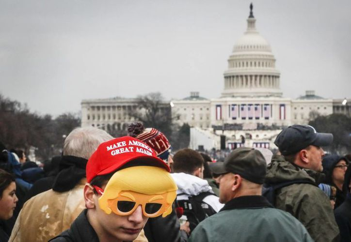 Cientos de personas aguardan frente al Capitolio, en WEashington, la ceremonia de juramentación de Donald Trump, como presidente de EU, esta mañana. (AP/John Minchillo)