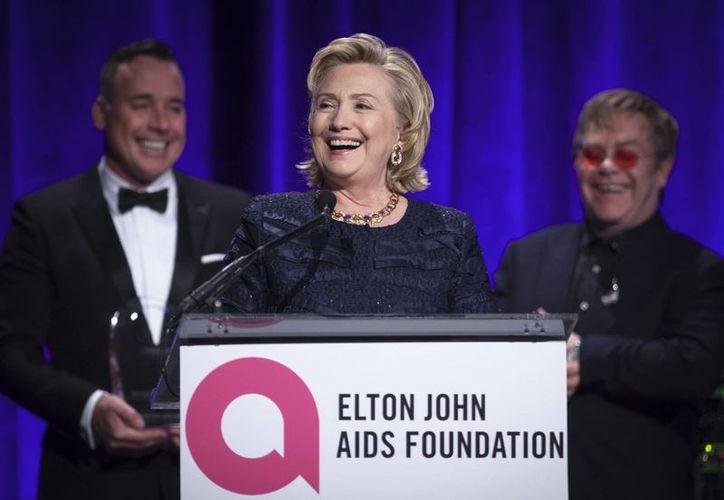 Hillary Clinton durante la gala, acompañada de Elton John (derecha) y su pareja David Furnish. (Agencias)