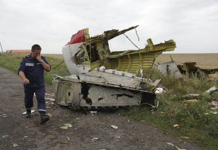 Un miembro de los servicios de rescate ucranianos se acerca al lugar donde se estrelló el avión Boeing 777 del vuelo MH 17 de la aerolínea Malaysia Airlines cerca de Donetsk. (EFE)