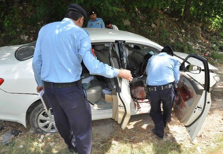Policías paquistaníes examinan el coche del fiscal Chaudhry Zulfikar que fue atacado por hombres armados en Islamabad, Pakistán. (Agencias)