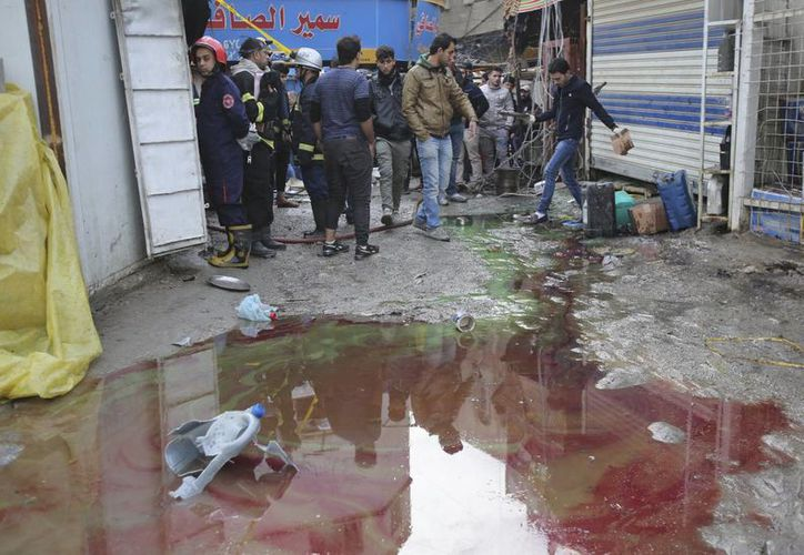Un grupo de iraquíes se reúne en el lugar de un ataque suicida en un concurrido mercado del centro de Bagdad. (AP/Karim Kadim)