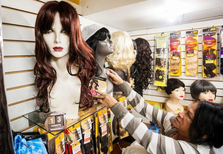 Un mujer observa varias pelucas  en una tienda en Venezuela. (EFE)