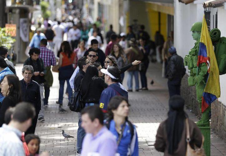 Peatones miran a un mimo callejero realizar una representación de un soldado de combate en Bogotá, Colombia. (Agencias)