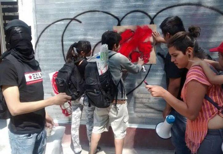 Jóvenes encapuchados hicieron pintas en estaciones de Metrobús en la Ciudad de México, durante la marcha de maestros de la CNTE. (Moisés Rafael Durán/Milenio)