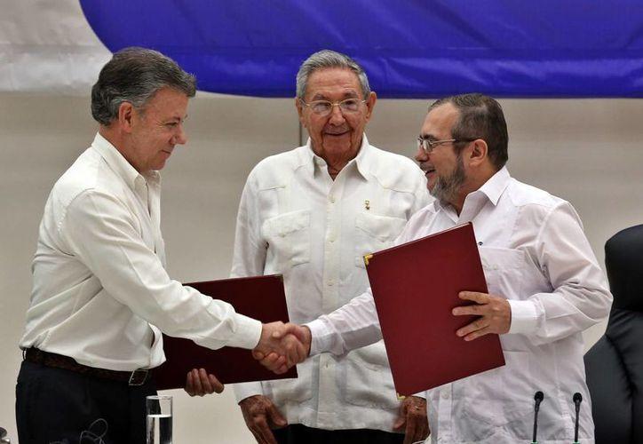 El máximo líder de las FARC en Cuba, Rodrigo Londoño Echeverri, alias 'Timochenko' (d) y el presidente de Colombia, Juan Manuel Santos (i) junto al presidente de Cuba, Raúl Castro (c) sostienen en sus manos el acuerdo para el cese el fuego, durante una ceremonia en La Habana. (EFE)