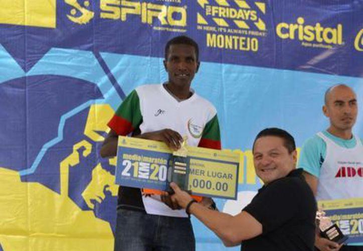 El vencedor de la carrera, recibiendo su cheque. (Milenio Novedades)