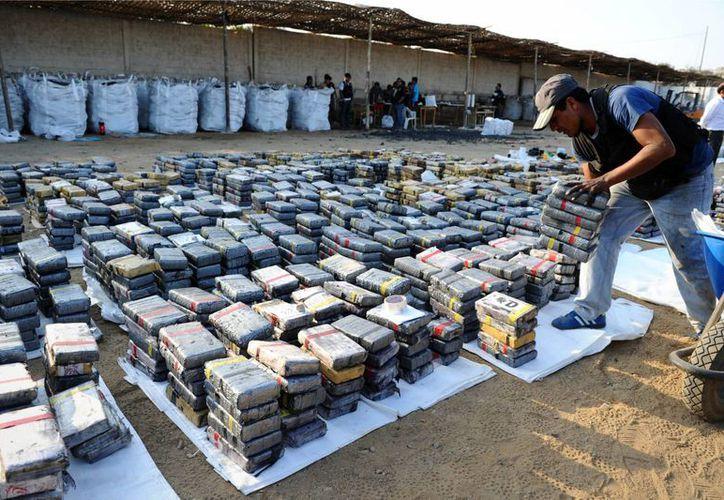 Un agente coloca los 'ladrillos' de cocaína encontrados en bloques de carbón la madrugada del pasado lunes en Huanchaco, Perú. (Foto: Ministerio del Interior de Perú/AP)