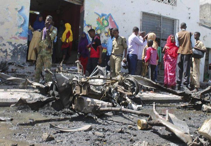 Oficiales de policía y vecinos congregados en el lugar tras la explosión de un coche bomba delante de un restaurante en Mogadiscio, Somalia. (EFE)