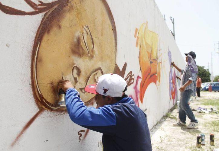 Desde temprana hora de ayer, más de 50 jóvenes amantes del graffiti se dieron cita para pintar las bardas de Turicun. (Jesús Tijerina/SIPSE)