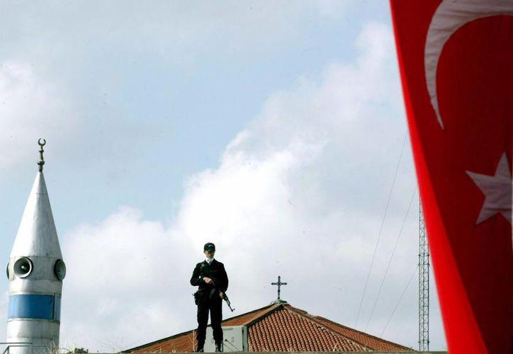 Un policía turco vigila entre una gigantesca bandera turca, el minarete de una mezquita (izq) y la cruz de una iglesia cristiana (c, detrás), en Estambul, Turquía. (Archivo/EFE)