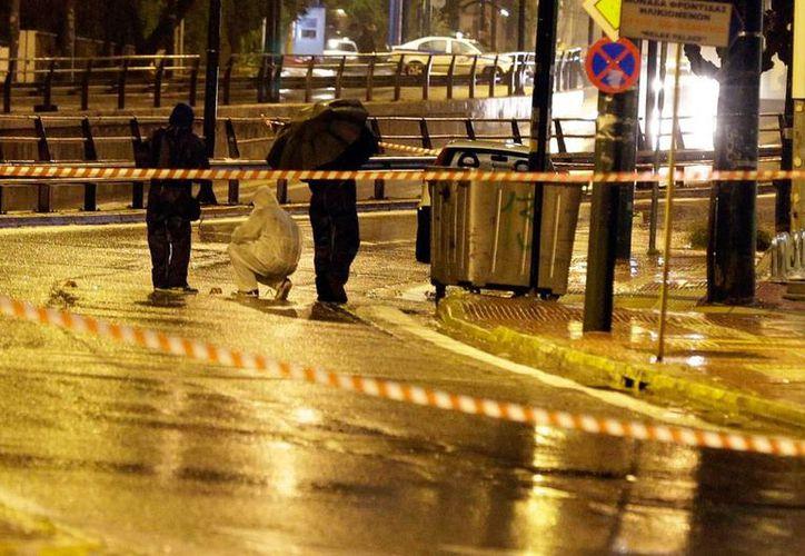 Peritos en balística recogen casquillos de balas que impactaron en las paredes de la Embajada de Israel en Atenas, Grecia. (AP)