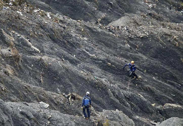 Miembros de los servicios de rescate caminan entre fragmentos del avión esparcidos por un área en los Alpes franceses, cerca de la localidad de Seyne-les-Alpes, en el sureste de Francia. (EFE)
