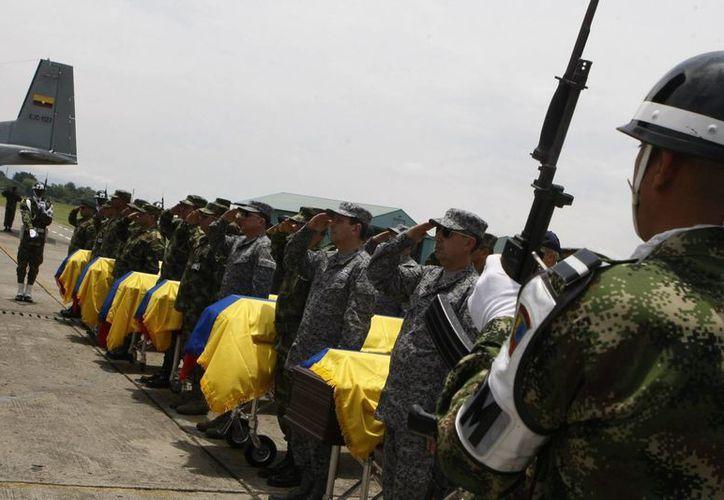 Soldados colombianos custodian los féretros de algunos de sus 11 compañeros muertos en un ataque de la guerrilla de las FARC en zona rural del municipio de Timba. (EFE)
