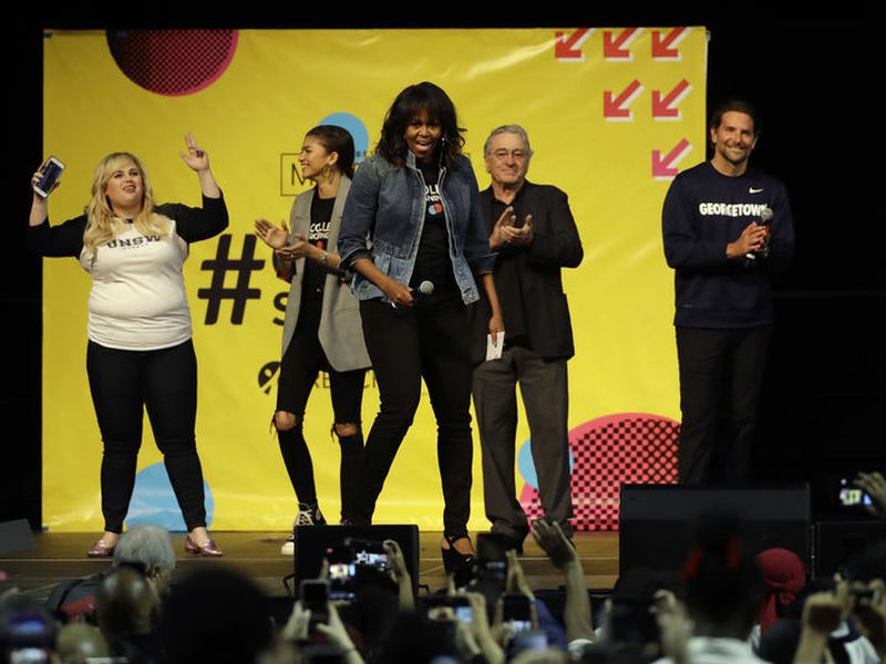 Michelle Obama, center, appears on stage as Rebel Wilson, background from left, Zendaya, Robert De Niro and Bradley Cooper look on at College Signing Day. (AP)