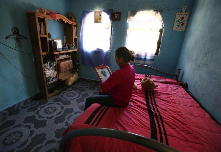 Afrodita Mondragón, madre de Julio César Mondragón, estudiante universitario asesinado en Iguala, mira el retrato de su hijo en su habitación que la mantiene como él la dejó. (Agencias)