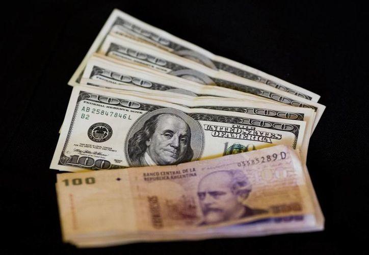 Argetina anunció el fin de los controles para la compra y venta de dólares vigentes desde diciembre de 2011, sin aclarar cuál será la cotización de la divisa, lo que generó incertidumbre por el impacto de la devaluación sobre la economía. (AP)