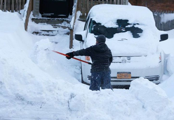 Una residente de Buffalo, Nueva York, intenta despejar de nieve el área donde se encuentra estacionado su vehículo. La tormenta invernal prácticamente ha sepultado el Estado. (AP)
