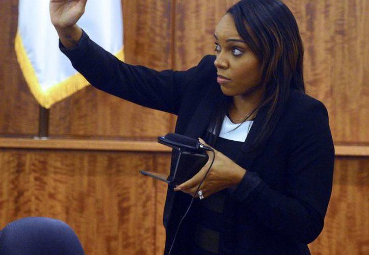 Shayanna Jenkins, prometida del exjugador de la NFL, Aaron Hernández, muestra durante un jucio por asesinato el tamaño que tenía la caja que tiró a la basura por indicación de él. Dicha caja tal vez contenía el arma homicida. (Foto: AP)