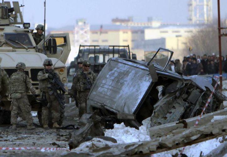 Soldados de la OTAN de la Fuerza Internacional de Asistencia para la Seguridad (ISAF) examinan la escena de un ataque suicida dirigido a un convoy en Kabul, Afganistán. (EFE/Archivo)