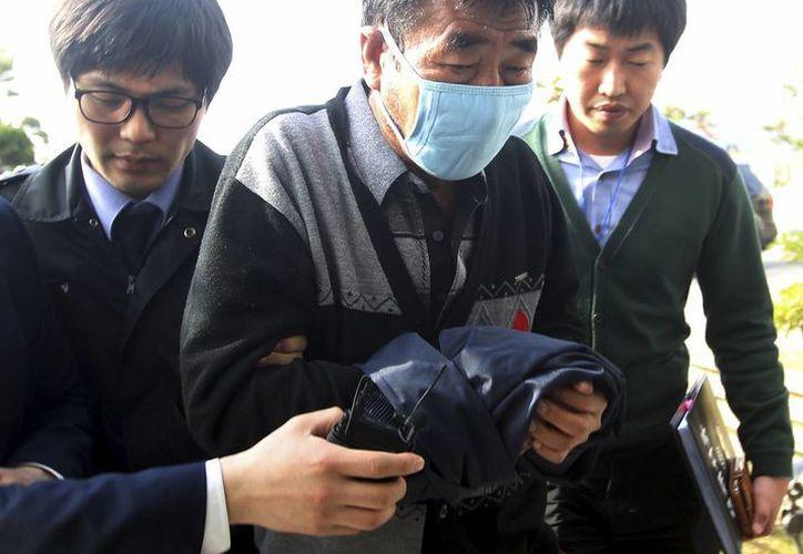 Lee Joon-seok, capitán del buque Sewol que se hundió en la costa de Corea del Sur, a su llegada al cuartel de la policía en Mokpo, al sur de Seúl, el 19 de abril de 2013. (Foto de AP/Yonhap, archivo)