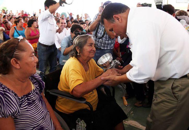 En Dzoncauich distribuyeron molinos de mano. En la imagen, Rolando Zapata hace la entrega a una mujer de la localidad. (Milenio Novedades)