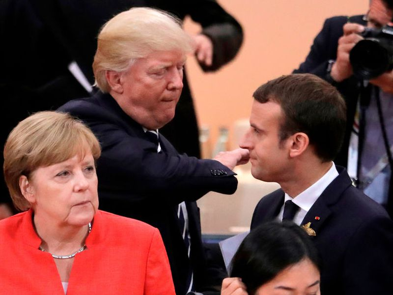 German Chancellor Angela Merkel, front, looks on as U.S. President Donald Trump, center, pads the shoulder of France's President Emmanuel Macronm in Hamburg, northern Germany. (AP)