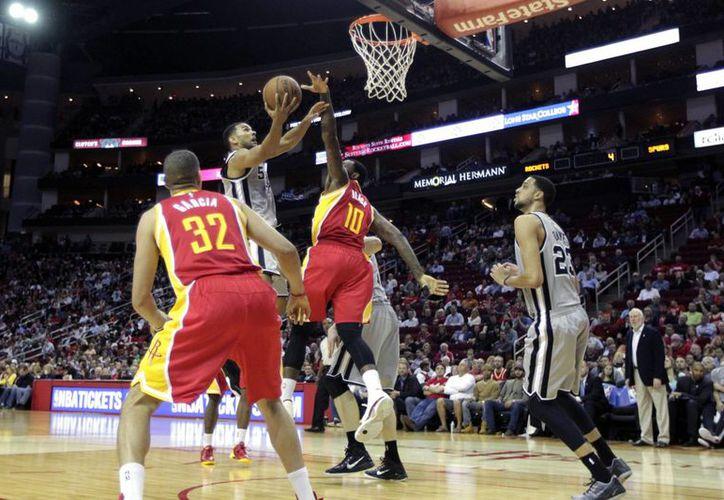 El guardia de Rockets, Corey Joseph (5), trata de encestar sobre la marca de Tarik Black (10), de Spurs, durante el tercer cuarto del duelo entre ambos equipos.  (Foto: AP)