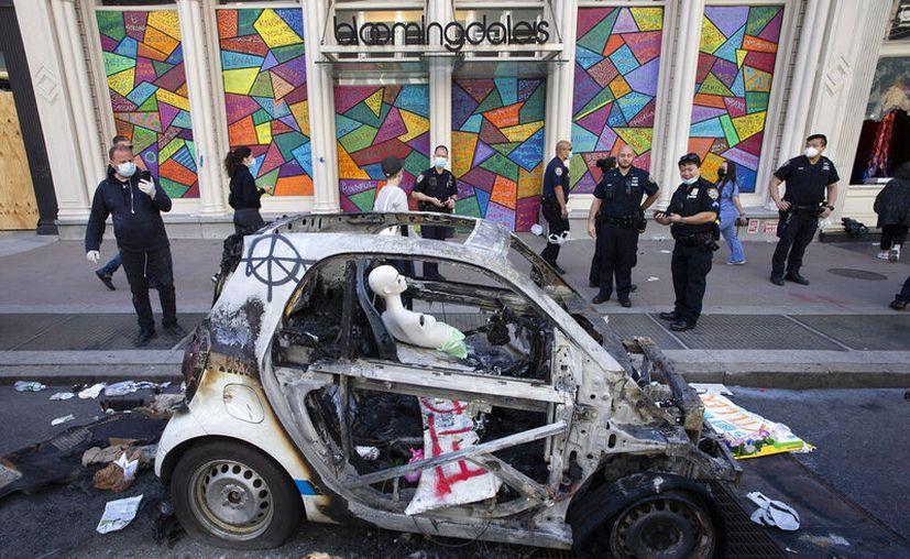 Policías observan un vehículo calcinado, el lunes 1 de junio de 2020, en SoHo, Nueva York, luego de una noche de protestas por la muerte de personas negras a manos de la policía. (AP Foto/Mark Lennihan)