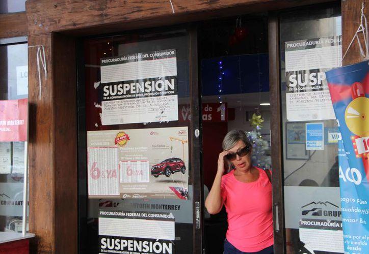 Las ventanas del negocio tienen varios sellos de suspensión de la Profeco. (Paola Chiomante/SIPSE)