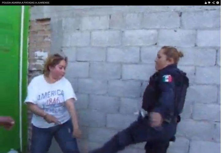 La mujer policía lanza una patada y un puñetazo a la ciudadana. (Captura de pantalla de video de Youtube)