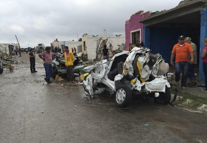 Fotografía de un grupo de personas que miran incrédulos un vehículo destrozado debido al paso de un tornado en Ciudad Acuña, Coahuila. (AP)