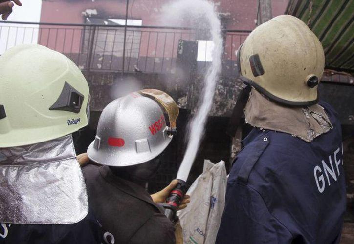 Bomberos rocían agua sobre lo que queda de la estructura de una gasolinera que explotó en Accra, Ghana. Las inundaciones arrastraron combustible almacenado hacia un incendio cercano lo que provocó una gran explosión que mató a varias personas y provocó incendios en construcciones cercanas. (Foto AP/Christian Thompson)