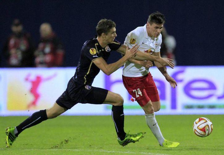 Christoph Leitgeb (d), del club Salzburg, pelea por el esférico con Jozo Simunovic, del Dínamo de Zagreb, en  casa de este último equipo dentro de la fase de grupos de la Liga Europa de la UEFA. (Foto: AP)