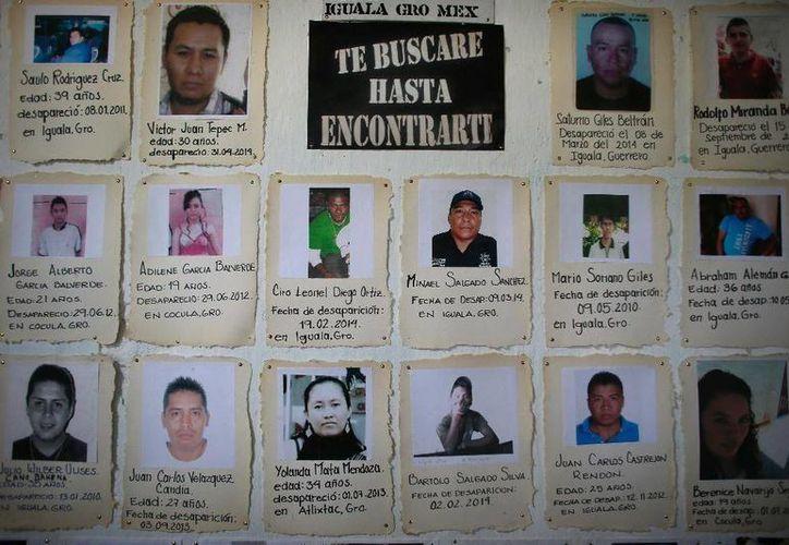 Fotos con una breve descripción de personas desaparecidas en un tablero de la parroquia católica de San Gerardo en Iguala. (Agencias)