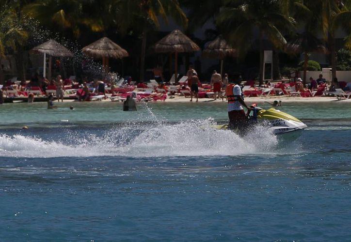 En un intento por controlar la moto se mezclaron entre las personas que chapoteaban en el agua. (Israel Leal/SIPSE)