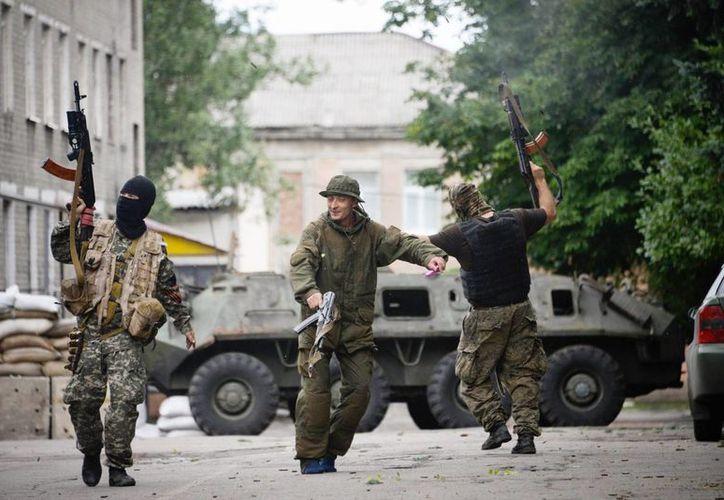 Varios rebeldes prorrusos bailando y disparando al aire mientras celebran el haber tomado control de un puesto de las antiguas tropas de Interior en Donetsk, Ucrania. (EFE)