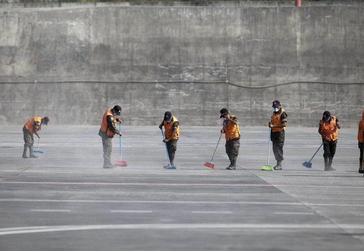 Una cuadrilla de trabajadores limpian las pistas del aeropuerto internacional La Aurora, de Guatemala, donde el volcán de Fuego ha estado activo. (AP)