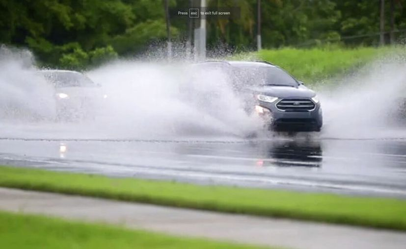 En esta imagen, tomada de un video, autos conducen por una carretera inundada en Canovanas, Puerto Rico. (AP Foto)