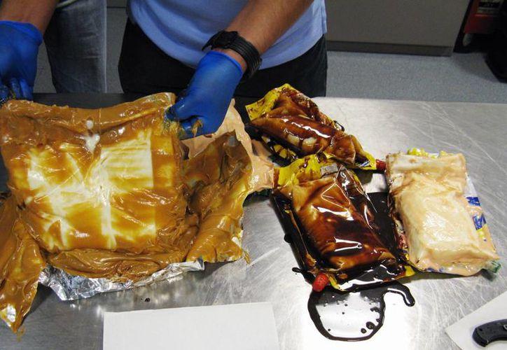 Un adenge aduanero muestra el interior de un paquete de chocolate líquido que oculta un cargamento de cocaína, en Los Ángeles. (Agencias)
