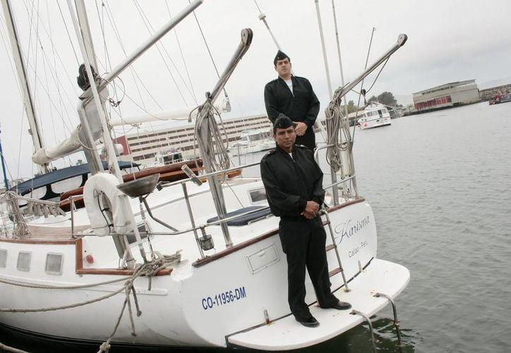 Dos marinos custodian el velero Karisma en la Escuela Naval del Perú en el Callao. (EFE)