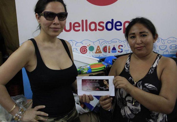 La cantante entregó el donativo a la representante de la asociación. (Tomás Álvarez/SIPSE)